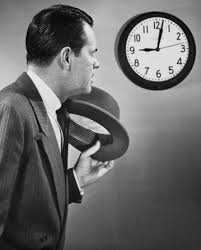 the importance of punctuality   the art of manlinessvintage man businessman hat off looking at clock