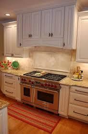 kitchen cabinets with granite countertops: new venetian gold granite countertops travertine backsplash white kitchen cabinets wood flooring area rug