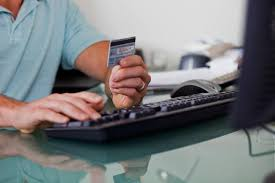 top 10 job scam warning signs man holding credit card while working at computer