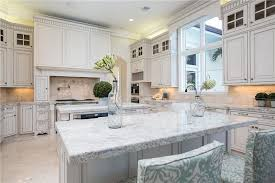 beautiful white kitchen cabinets: luxury kitchen with white cabinetry giallo fantasia granite counter center island dining island