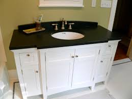 dark countertop white bathroom cabinets under framed mirror and grey floor mat over white bathroom black and white bathroom furniture