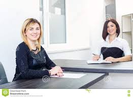 two women sitting at a table in the office blonde and brunette on two women sitting at a table in the office blonde and brunette on job interview