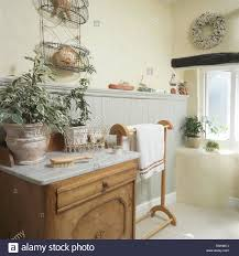 washstand bathroom pine: green plants in pots on marble topped washstand in cottage bathroom with an old pine towel rail