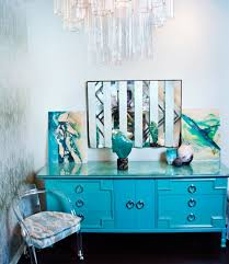 hollywood regency office features art deco chandelier over striped mirror over turquoise credenza accented with ring pulls and turquoise trim moldings art deco office credenza