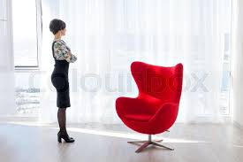 portrait of a young woman psychologist therapist in a bright office beautiful modern space with red chair for the client consulting psychologist in the beautiful bright office