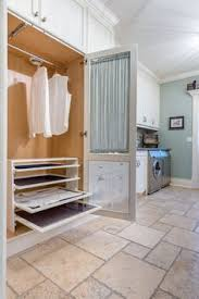 multiple drying racks and a hanging rod all behind a lovely curtained screened door what a charming laundry room feature bright modern laundry room