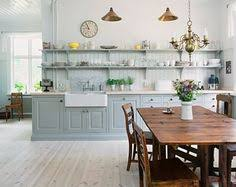 this small change will make any kitchen feel open and airy and its perfect for showing off collections pretty glassware blue cabinet kitchen lighting
