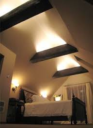 the exposed rafter beams mean greater ceiling height and they look cool could drop a light fixture between beams rather than have the beams lit beams lighting