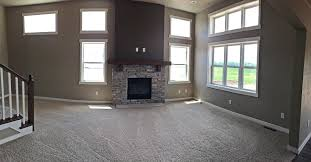 this spacious great room features an abundance of large windows allowing for natural light to fill the space also displayed is a cultured stone gas allowing natural light fill