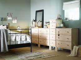 a bedroom with a large black iron bed shown together with solid pine chest of drawers bedroom furniture in ikea