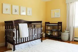 banana yellow walls stand over natural hardwood flooring with thick shag white rug in this nursery baby nursery yellow grey gender neutral