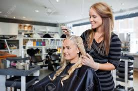 stock photo young woman having her hair dyed by beautician at parlor beautician jobs