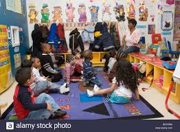 african american preschool teacher student in stock photos african american preschool teacher reading a book to her class stock image