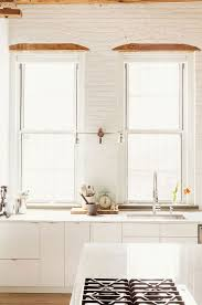 white kitchen windowed partition wall: view in gallery kitchen in white with exposed brick walls and large windows