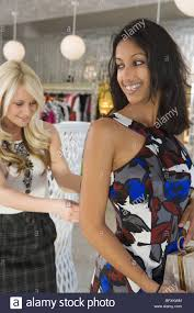 store assistant helps w dress stock photo royalty stock photo store assistant helps w dress