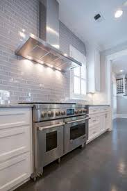 euro week full kitchen: white and gray kitchen features white cabinets paired with white and grey granite counters and a