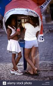metre giant umbrella: two girls in telephone kiosk draped in a giant santa claus hat pelourinho salvador