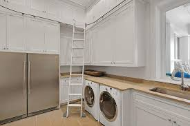 well appointed laundry room and pantry combo is fitted with stainless steel extra refrigerators positioned side by side beneath stacked white cabinets beach style laundry room