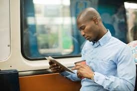 top 10 recruitment marketing to follow in 2016 recruitics african man commuting on subway while working digital tablet he has a coffee in