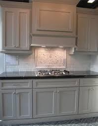 euro week full kitchen: gray cabinets black counters slate herringbone floor marble hex backsplash accent
