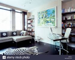 faux zebra skin rug on black flooring in modern home office with laptop computer on glass table black home office laptop