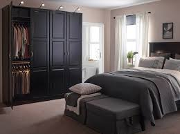 a large bedroom with a black bed and bedside tables shown together with a large bedroom furniture at ikea