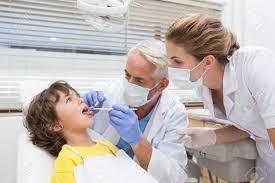 pediatric dentist examining a little boys teeth his assistant pediatric dentist examining a little boys teeth his assistant at the dental clinic stock photo