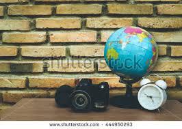 globe clock and camera on desk with old dirty brick wall brick desk wall clock