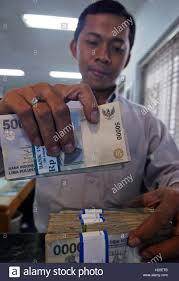 an n foreign exchange employee holds rupiah bills in an n foreign exchange employee holds rupiah bills in jakarta 5 2005 the n rupiah is undervalued and its weakness is caused by