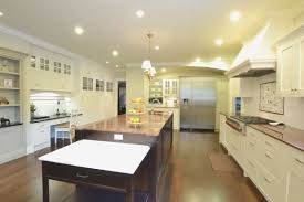 recessed lighting in white ceiling with pendant lamp also dark brown island with granite countertop also kitchen art deco kitchen lighting