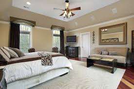 couch bedroom sofa: a spacious master bedroom with a deep tray ceiling and a large ceiling fan against